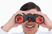 Close up of smiling young tradesman looking through binoculars — Photo