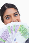 Close up of female entrepreneur hiding her face behind bank note — Stock Photo