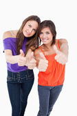Teenagers putting their thumbs up while smiling — Stock Photo