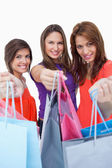 Smiling young women showing their purchases in front of the came — Stock Photo