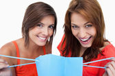Two teenage girls holding a purchase bag while smiling — Stock Photo