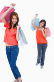 Teenage girl following her friend after shopping against a white — Stock Photo