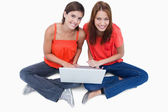 Smiling teenage girls sitting with a laptop on legs while lookin — Stock Photo