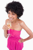 Young female looking to the side with a hand on her hip and drin — Stock Photo