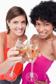 Glasses of white wine being happily clinked by two young females — Stock Photo