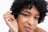 Young brunette applying mascara — Stock Photo