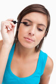 Young woman almost closing her eyes while applying mascara — Stock Photo