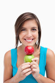 Teenager smiling and holding two apples between her hands and he — Stock Photo