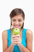 Smiling teenager looking at a green apple placed on her hands cr — Stock Photo