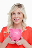 Smiling teenage girl holding a pink piggy bank in her hands — Stock Photo