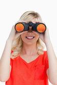 Smiling woman looking through binoculars — Stock Photo