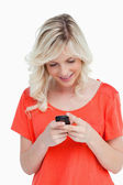 Smiling woman sending a text with her mobile phone — Stock Photo