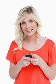 Woman beaming while sending a text with her cellphone — Stock Photo