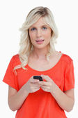 Woman looking at the camera while sending a text with her mobile — Stock Photo