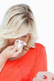 Junge frau niesen halten einige tabletten — Stockfoto