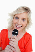 Smiling teenager singing in a cordless microphone — Stock Photo