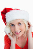 Young blonde woman putting on the Santa Claus hat — Stock Photo