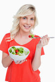 Young smiling woman eating a fresh salad with a fork — Stock Photo