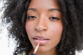 Young woman using a lip gloss applicator to make-up — Stock Photo
