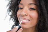 Young smiling woman making-up while using a lip gloss applicator — Stock Photo