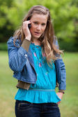 Teenage girl using her mobile phone while looking at the camera — Stock Photo