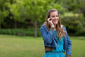 Teenage girl standing in the countryside while talking on the ph — Stock Photo