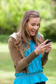 Happy teenage girl receiving a text on her cellphone while stand — Stock Photo