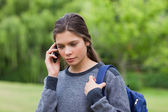Thoughtful young girl using her mobile phone while carrying her — Stock Photo