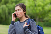 Young calm girl talking on the phone while looking towards the s — Stock Photo