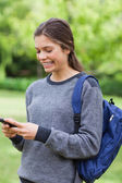 Smiling young girl sending a text with her mobile phone — Stock Photo