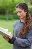 Young relaxed adult reading a book in the countryside — Stock Photo