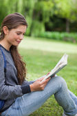 Young smiling woman reading a book while sitting on the grass in — Stock Photo