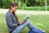 Young relaxed adult reading a book while sitting on the grass — Stock Photo