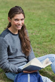 Smiling young adult holding an open book while sitting on the gr — Stock Photo