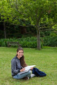 Smiling teenage girl doing her homework while sitting down in a — Stock Photo