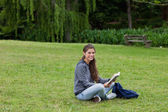 Smiling young adult reading a book while sitting cross-legged — Stock Photo
