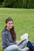Young smiling girl sitting cross-legged while holding a book — Stock Photo