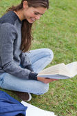 Young smiling woman holding a book while sitting cross-legged — Stock Photo