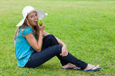 Young smiling girl eating a green apple while sitting on the gra — Stock Photo