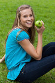 Smiling young woman holding a green apple while sitting in a par — Stock Photo