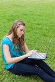 Mladá uvolněná žena pomocí její laptop, zatímco sedí na trávě — Stock fotografie