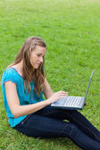 Young relaxed woman using her laptop while sitting on the grass — Stock Photo
