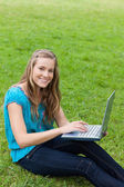 Young attractive girl looking at the camera while using her lapt — Stock Photo