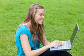 Young attractive girl looking at her laptop while sitting in the — Stock Photo