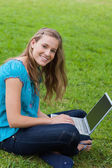 Young smiling girl looking at the camera while using her laptop — Stock Photo