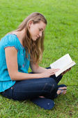 Serious young girl reading a book while sitting in a park — Stok fotoğraf