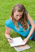 Young serious girl lying on the grass in a park while writing on — Stock Photo