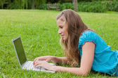 Side view of a young girl typing on her laptop while lying down — Stock Photo