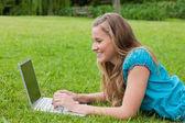 Jovem sorridente, olhando para o laptop dela enquanto está deitado — Fotografia Stock
