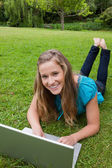 Smiling teenage girl looking at the camera while lying on the gr — Stock Photo